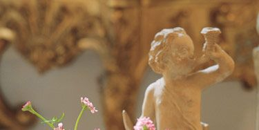 Terra-cotta putto heralds floriferous season in the garden. Whirligigs of pink scabiosa in a porcelain vase.