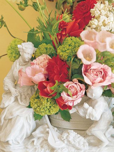 Porcelain figures frolic amongst Canterbury bells, viburnum, striped roses and red dahlias.