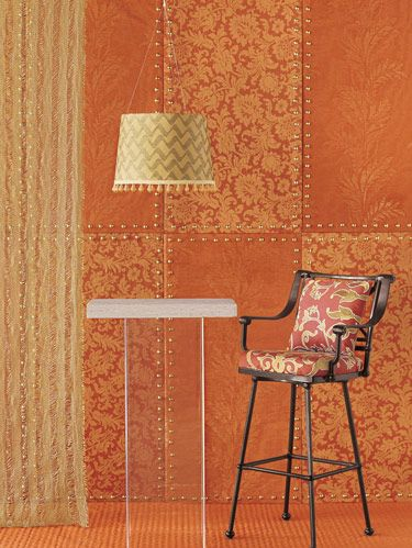 """Orange embraces gold metallics in regal patterning enhanced with sheers, nailheads and glass trim. SHEER: Pindler & Pindler's gold """"Laughlin.""""  BACKGROUND PANELS: Houlès nailheads delineate panels with subtle florals on """"Servandoni,"""" designed by Matthew Patrick Smyth for Schumacher, and Carole Fabrics' pronounced patterning in """"Swan Hill."""" LAMPSHADE: Fabricut's """"Pismo Zig"""" in gold with """"Rialto"""" handblown glass trim designed by Lori Weitzner for Samuel & Sons. CUSHIONS: Manuel Canovas' """"Tolède"""" in coral on Woodard barstool. FLOOR: Highland Court's quilted chintz linen/cotton """"San Marco"""" in tangerine designed by Philip Gorrivan. Travis Acrylic pedestal table with Paris Ceramics' """"Bordeaux"""" limestone top."""