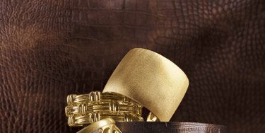 "COUNTERCLOCKWISE, FROM TOP: Brazilian designer Carla Amorim's 18k satin finish cuff atop Valentin Magro's 18k gold Layered Bamboo flexible cuff. Elizabeth Rand's 18k brushed gold cuff. David Yurman's 18k Woven Cable cuff. Matioli's 18k Hiroko bombe cuff atop David Webb's 18k Corrugated hammered gold cuff. BACKGROUND: Pindler & Pindler's copper ""Aztec"" faux animal skin."