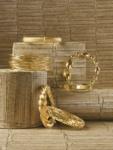 "Clockwise, from top: Medium-ridged Column bangle in 18k yellow gold from Slane & Slane. Faraone Mennella's Tuka-Tuka Big Ball bangle in 18k gold. Cartier's 18k Love bracelet. John Hardy's 18k Kali oval bangle. Crazy Twist bracelet in 18k yellow gold by Jean Schlumberger for Tiffany & Co. Ippolita's 18k Squiggle bangles. background: Maya Romanoff's ""Komodo"" Type II vinyl."