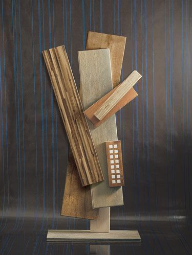 """<p>A cubist-style sculpture of wood flooring samples elucidates the wealth of possibilities for floor décor, including bleached walnut and camel-bone inlays.</p>  <p>VERTICAL BOARDS, FROM TOP: Haifa Wood's Oak #102 and its lighter oak #214, topped by De Ferranti's waxed teak with camel-bone inlay squares. LEFT: BR-111's Corduroy's striped Macchiato Pecan hardwood. ANGLED BOARDS: Mirage's soft brown Natural Sapele wood with cashmere finish, topped by T. Morton's bleached walnut. FROM BOTTOM: Resting on Exquisite Surfaces' Campagne Gray French oak is T. Morton's white oak. Background is Maya Romanoff's """"Contrast Stitched Vertical"""" wallcovering, designed by David Rockwell.</p>"""