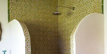 "<p><strong></strong>When it comes to creating a transporting experience in a bathroom, consider the tile first. For one client, Ireland was tasked with creating a space that felt as if it were ""somewhere exotic, like Mexico or Morocco,"" so she ordered dozens of custom lime-and-white patterned tiles from Mosaic House NYC to line the corner shower and bathroom walls. The tiles are a fun contrast to the pinks and purples of the graphic rug and Mexican folk-art chair.</p>"