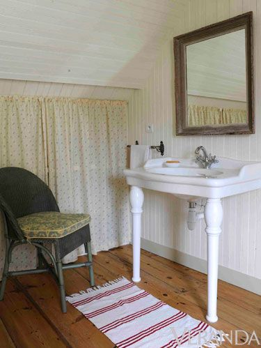 <p>A simple, cream-colored curtain with a delicate floral pattern added charm to the attic bathroom, and it also served as an easy way to hide storage shelves. These details, combined with the worn frame of the mirror and the vintage-style freestanding sink, embraced the home's 100-year heritage while giving it a real point of view.</p>