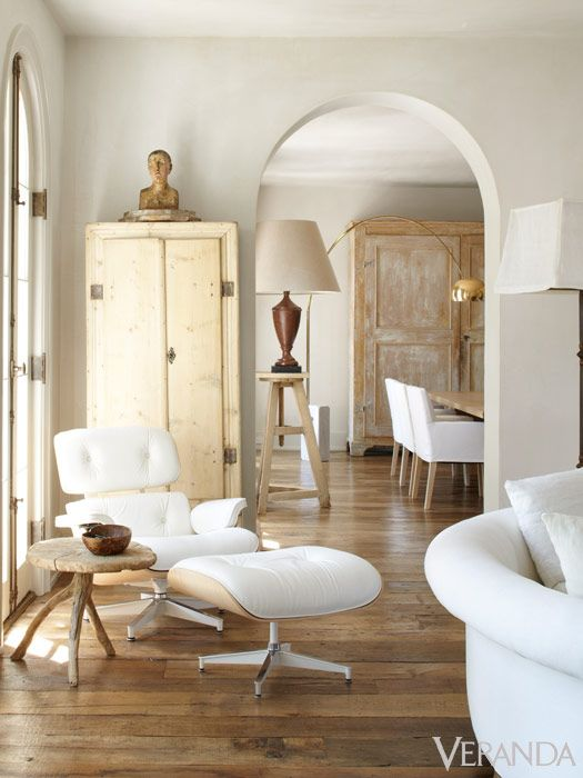 Modern white Eames lounge chair and ottoman with rustic wood stool in French Country living room. Design by Pamela Pierce. #midcenturymodern #eames #modernfrench #frenchcountry #livingroomdecor #pamelapierce