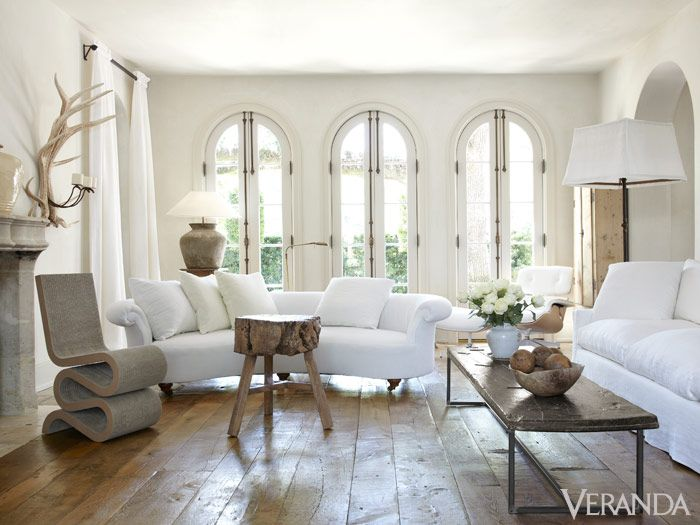 French Country Interior Design Ideas: Pamela Pierce living room with white furniture, rustic coffee table, modern chair and French limestone fireplace. #interiordesign #frenchcountry #livingroomdecor #pamelapierce