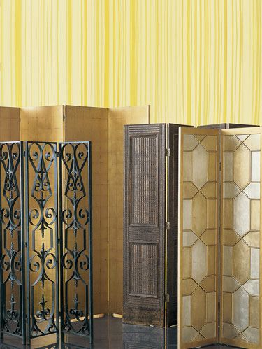 """<p><b>BACKGROUND SCREEN: </b>Alfonso Marina's 90.5"""" six-panel, handgilded Arnaud screen stands tall. FOREGROUND FROM LEFT: Uttermost's four-panel Ashen screen in handforged, handhammered metal has gray finish. Chelsea House's antiqued wood Nailhead screen has contrasting matte and shiny surface. Decorative Crafts' four-panel #3073 screen is finished in silver leaf and animated with raised hexagonal patterning fashioned in antiqued wood. <b>BACKGROUND FABRIC: </b>Création Baumann's """"Sinfonia"""" sheer in 219. See Sources on page 206. </p>"""