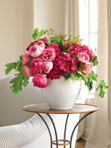 Pink garden roses, hydrangeas and huckleberry branches enhance a glazed French pot.