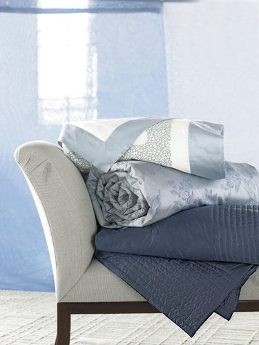 "Frette's embroidered cotton sateen sheet ""Eva Sfere Ricamo,"" ""Eva Fiore Arredo"" floral duvet and Atlantic blue silk taffeta ""Rainbow"" quilt on Maxine Snider's chaise."
