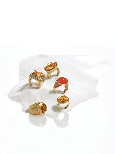 CLOCKWISE FROM TOP: Bezel-set, 12-carat citrine ring in 18k gold from Laura Pearce. Jenny Perl's cabochon carnelian ring with diamonds and orange sapphires in 18k gold. Marco Bicego's lemon citrine Jaipur ring in 18k gold. Elizabeth Rand's Madeira citrine Zebra ring with diamonds in 18k gold. David Yurman's champagne citrine and diamond Albion ring crafted in 18k gold.