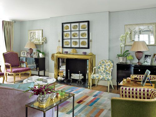 "Nina Campbell's damask pops on the chairs, beside the fireplace. Gilded lotus leaves hang over the Art Deco mantle with custom mirror detailing. <a href=""http://www.lucycope.com"" target=""_blank"">Lucy Cope Limited</a> lamps rest on the Biedermeier chests. Sofa by <a href=""http://www.niermannweeks.com"" target=""_blank"">Niermann Weeks</a> in a Campbell fabric. Circular print by <a href=""http://www.galbraithandpaul.com"" target=""_blank"">Galbraith & Paul</a> on chair. A brightly colored <a href=""http://www.therugcompany.info/html/tags"" target=""_blank"">The Rug Company</a> carpet anchors the room."