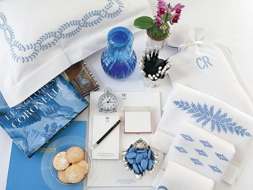 "The blue and white Italian pillow sham off-sets the Carafe by <a href=""http://www.dior.com"" target=""_blank"">Dior</a>. An unexpected orchid stands tall in a mint julep cup from India. A hot water bottle in a piqué fabric offers guests a comfortable companion. Embroidered hand towels and mints in a sterling shell add a personal touch to the collection."