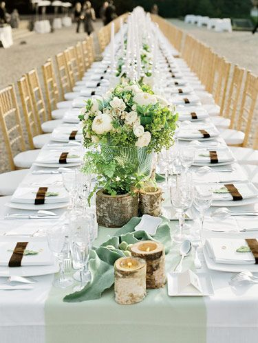 Fuzzy baby almonds, pepper berries, and porcelain doves accompany birch-bark vessels and white and green florals down the length of the reception dining table. Paris-based floral designer Stephane Chapelle helped bring to life the rustic and refined table stylings along with the bride. Prior to the grand event the two drove around in Stephane's flower truck out at <i>Rungis</i> — the endless flower, fruit, and vegetable market outside of Paris — to hand select each element.