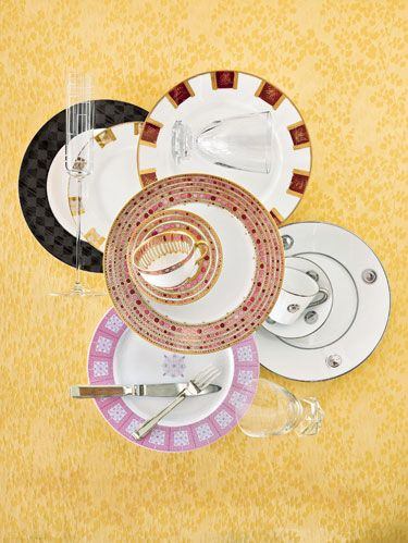"""<p>Clockwise from top left: <a href=""""http://www.noritake.com"""" target=""""_blank"""">Noritake's</a> """"Zinc2"""" plate with diamond border. Versace's """"Dedalo"""" champagne flute for <a href=""""http://www.rosenthalusa.com"""" target=""""_blank"""">Rosenthal</a>. <a href=""""http://www.puiforcat.com"""" target=""""_blank"""">Puiforcat's</a> sand/violet """"Variations"""" plates with <a href=""""http://www.baccarat.com"""" target=""""_blank"""">Baccarat's</a> """"Abysse"""" stemless crystal water goblet, designed by Thomas Bastide. <a href=""""http://www.bernardaud.fr"""" target=""""_blank"""">Bernardaud's</a> platinum geometric """"Ithaque,"""" designed by Olivier Gagnère. Baccarat's """"Abysse"""" goblet. <a href=""""http://www.jchewporcelain.com"""" target=""""_blank"""">J.Chew's</a> lavender """"Lattice"""" plate with <a href=""""http://www.ralphlauren.com"""" target=""""_blank"""">Ralph Lauren's</a> """"Maddox"""" silverware.</p><p> Center: Robert Haviland and C. Parlon's jewel-like """"Syracuse Rose"""" for <a href=""""http://www.mottahedeh.com"""" target=""""_blank"""">Mottahedeh</a>.</p><p>Background: <a href=""""http://www.marthastewart.com"""" target=""""_blank"""">Martha Stewart</a> tablecloth. </p>"""