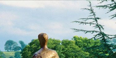 The rough abstract shape of a seated woman, gleams in the twenty-acre urban garden.