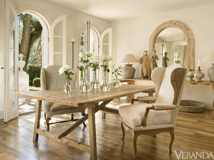 French Country dining room with farm table, wing chairs, and arched French doors to the glorious garden. #frenchcountry #diningroom #pamelapierce