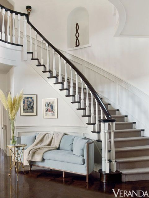 The lunette sofa echoes the curve of the staircase.
