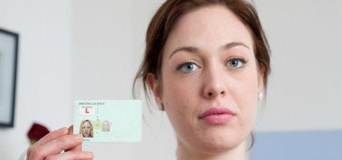 pale woman holding photo id