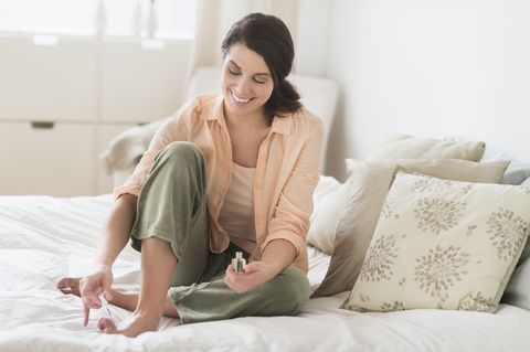 USA, New Jersey, Jersey City, Woman doing pedicure in bedroom