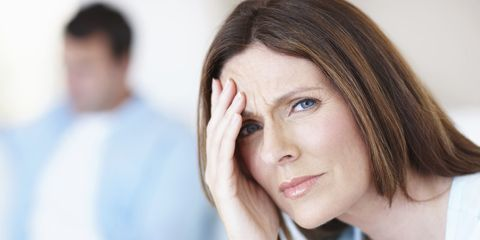 Woman with headache, husband in background
