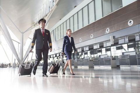 Pilot and Flight Attendant Walking Through Airport
