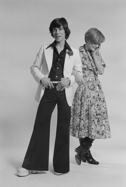 English singer David Van Day, of pop group Guys 'n' Dolls, and a young woman, modelling fashionable outfits, 24th March 1975. (Photo by Michael Putland/Getty Images)