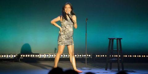 Human body, Dress, Human leg, Microphone, Standing, Entertainment, Audio equipment, Stage, Beauty, Fashion,