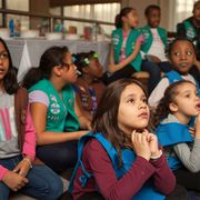 Girl scout troop listens at a meeting.