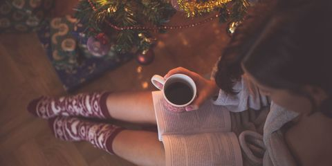 reading book in front of christmas tree