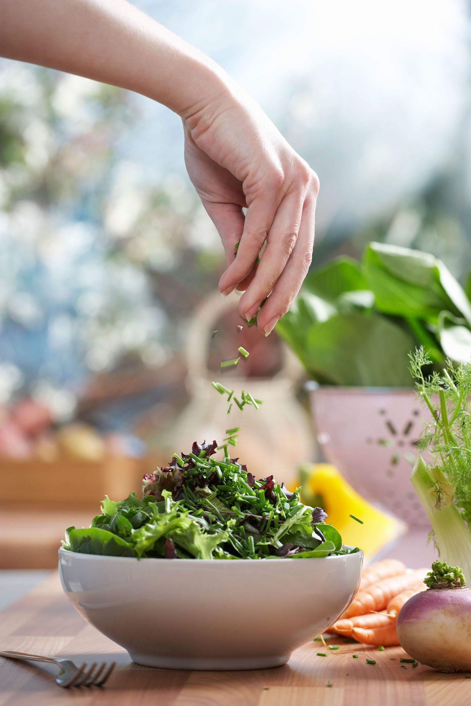 woman sprinkling her salad