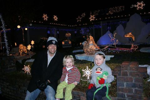 A father sitting in front of christmas decorations with his two kids
