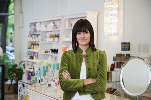 young stylish woman at makeup counter in store