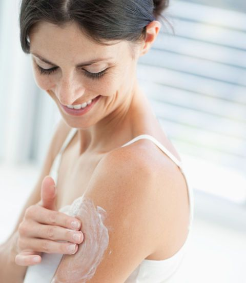woman rubbing lotion on her arm
