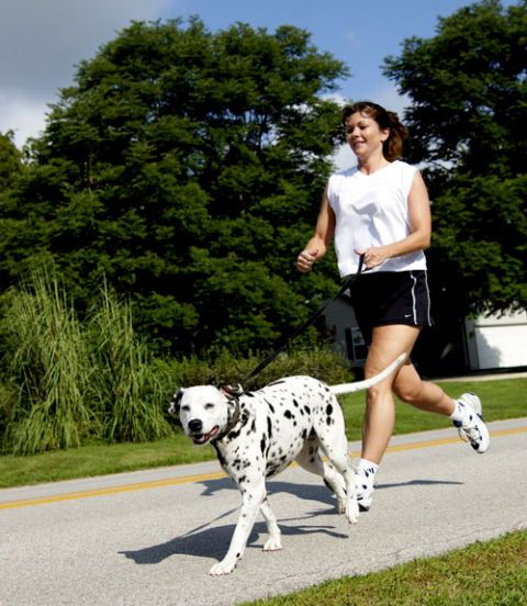 woman running with dalmation