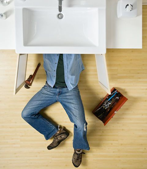 man fixing sink