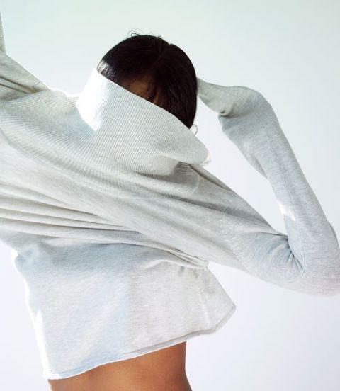 woman putting on a shirt