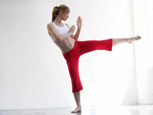 woman doing kickboxing in red sweatpants