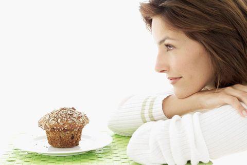 woman staring at muffin