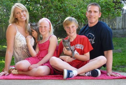 young blonde family holding gray kittens
