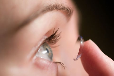 woman putting in contacts