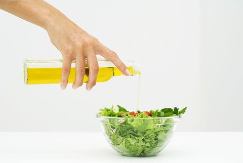 woman pouring oil in salad