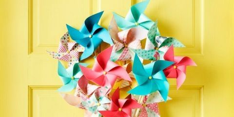 """<p><strong>Materials</strong></p> <p>• 12 paper pinwheels ($8 for set of 12; <a href=""""http://www.etsy.com/"""" target=""""_blank"""">OhMyDearBoutique.Etsy.com</a>)</p> <p>• Hot-glue gun and glue sticks</p> <p>• 12 wooden dowels, 2' x ¼"""" diameter ($3.49 for pack of 12; <a href=""""http://www.michaels.com/"""" target=""""_blank"""">Michaels.com</a>)</p> <p>• Masking tape</p> <p>• Woven ribbon ($3.99; <a href=""""http://www.joann.com/"""" target=""""_blank"""">Joann.com</a>)</p> <p>• Scissors</p> <p>• Fishing line</p> <p><strong> </strong></p> <p><strong>Directions</strong></p> <p><strong>1. </strong>Carefully remove the pinwheels from their sticks. Hot-glue paper pinwheels to the ends of dowels and let set.</p> <p><strong>2. </strong>Create a center column by lining up three dowels. Stagger the heights so the pinwheels can sit about ¼"""" from each other. Hot-glue the dowels together; let set.</p> <p><strong>3. </strong>Cross another dowel over the center column and hot-glue them together; let set. Continue crossing dowels until you create a tight arrangement, making sure to apply the glue in the same general area each time and holding it in place until it sets.</p> <p><strong>4. </strong>Neatly wrap masking tape around the glued area, then wrap woven ribbon around the tape and secure at the back with a dot of hot glue; let set.</p> <p><strong>5. </strong>Cut a piece of fishing line and tie it to the center dowel column. Create a loop to hang.</p>"""