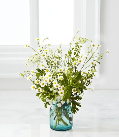 <p>TIME: 25 minutes<br /> <strong>Materials</strong></p> <p>Floral shears<br /> Small white cup or vase<br /> Geranium<br /> Mint<br /> Queen Anne's lace<br /> Sunflowers<br /> Chamomile<br /> Nigella</p> <p><strong>Directions</strong></p> <p>1. Use the floral shears to trim the bottom of a few geranium stems. Cluster them at the base of the vase, allowing the leaves to drape over the sides. <br /> 3. Trim about two or three sprigs of mint and tuck them in on different sides of the arrangement, filling empty areas between the geranium leaves. <br /> 4. Insert about three or four trimmed stems of Queen Anne's lace at the far edges of the vase, varying the height and choosing pieces that have already bloomed, as well as ones that are just budding. <br /> 5. Select seven or eight sunflowers and trim to different heights, keeping some the same length as the Queen Anne's lace and the others a bit taller. Group a few on one side of the vase, and turn the faces of the flowers in slightly different directions for a less formal feel. Place one opposite the group to create a low, oval shape. If the flower heads are too heavy to stand on their own, lean them against the hardy mint sprigs for support.<br /> 6. Cut a small bunch of chamomile and place just off center. Add some sparser pieces to break up overly green patches. <br /> 7. Select a handful of wispy nigella and cut them just longer than the Queen Anne's lace, adding to fill in any last gaps and complete the shape.</p> <p><strong>DIY Tips:</strong></p> <p>1. Try a footed, opaque vessel for an interesting bouquet silhouette. Bonus: Stems won't distract.</p> <p>2. To create whimsy, play with scale, like these small chamomile blossoms and larger sunflowers.</p> <p>3. Position hardy greenery (here, mint sprigs) to hold up heavy flower heads.</p>