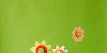 <p>Turn scrap paper and extra buttons into quirky, colorful flowers, which you can turn into wall art, displays, journals and more! Flip through to learn how to make the flowers.</p> <p><strong>MATERIALS</strong></p> <p>     · Scrapbook paper</p> <p>     · Scissors</p> <p>     · 3 buttons per flower: 1 large, 2 small</p> <p>     · Pencil</p> <p>     · Precut floral stem wire</p> <p>     · Wire cutters</p> <p> </p>