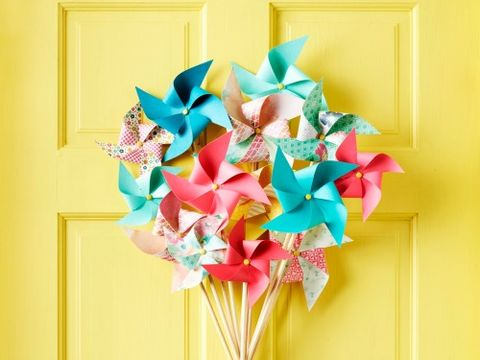 "<p><strong>Materials</strong></p> <p>• 12 paper pinwheels ($8 for set of 12; <a href=""http://www.etsy.com/"" target=""_blank"">OhMyDearBoutique.Etsy.com</a>)</p> <p>• Hot-glue gun and glue sticks</p> <p>• 12 wooden dowels, 2' x ¼"" diameter ($3.49 for pack of 12; <a href=""http://www.michaels.com/"" target=""_blank"">Michaels.com</a>)</p> <p>• Masking tape</p> <p>• Woven ribbon ($3.99; <a href=""http://www.joann.com/"" target=""_blank"">Joann.com</a>)</p> <p>• Scissors</p> <p>• Fishing line</p> <p><strong> </strong></p> <p><strong>Directions</strong></p> <p><strong>1. </strong>Carefully remove the pinwheels from their sticks. Hot-glue paper pinwheels to the ends of dowels and let set.</p> <p><strong>2. </strong>Create a center column by lining up three dowels. Stagger the heights so the pinwheels can sit about ¼"" from each other. Hot-glue the dowels together; let set.</p> <p><strong>3. </strong>Cross another dowel over the center column and hot-glue them together; let set. Continue crossing dowels until you create a tight arrangement, making sure to apply the glue in the same general area each time and holding it in place until it sets.</p> <p><strong>4. </strong>Neatly wrap masking tape around the glued area, then wrap woven ribbon around the tape and secure at the back with a dot of hot glue; let set.</p> <p><strong>5. </strong>Cut a piece of fishing line and tie it to the center dowel column. Create a loop to hang.</p>"