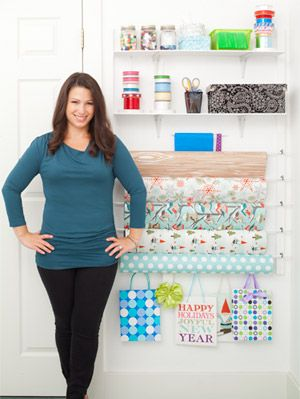"""<p>Portland, OR, freelance graphic designer Sarah Zimmerman had been mulling over a use for the blank wall in her laundry and craft room for a long time. """"Every week I had a new idea for the space. After two years I finally had a vision of a gift-wrap station,"""" says the craft blogger (<a href=""""http://www.repeatcrafterme.com/"""" target=""""_blank"""">RepeatCrafterMe.com</a>). Sarah had a plywood frame and shallow shelves cut to fit at her local Home Depot, then she bought cup hooks, dowels, D rings and paint—a haul that added up to a modest $31 in materials. """"My biggest splurge was the paint,"""" she says. """"I was dead-set on bright white."""" Once home, she enlisted her husband, Joel, to help her put together all the pieces and hang her new system on the wall. """"Now I'm not frantically fishing through bins of ribbons and tissue paper every time I need to wrap a gift,"""" says Sarah.</p> <p><strong>Sarah's Tips and Tricks</strong></p> <p><strong>You <em>can</em> take it with you</strong></p> <p>Rather than drill right into the wall, Sarah mounted the system on a piece of plywood, then hung it with wire. """"I can still use it if we move!"""" she says.</p> <p><strong>Be inspired by the pros</strong></p> <p>Sarah noticed how stationery stores display wrapping paper horizontally and craft stores keep ribbons on spools to make them easy to pull out and cut. She decided to do the same.</p> <p><strong>Stick to small-scale</strong></p> <p>Keep out only a few wrapping paper patterns to choose from. You'll have an incentive to use what you have before starting a new roll.</p> <p><strong>Adapt to your lifestyle</strong></p> <p>Since Sarah has two young boys, safety is a concern. She housed small and sharp items on the highest shelves and used plastic 3M hooks instead of metal ones for the gift bags within her toddlers' reach.</p> <p><strong>Make it truly custom</strong></p> <p>Hunting for the individual elements took more legwork, but it was worth the savings (a ready-made system can cost $100 or more"""