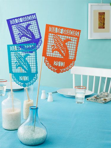 """<p><em>Papel picados</em> (""""perforated papers"""") are brightly colored flags hand-cut with intricate designs. Used on special occasions and holidays—Día de los Muertos, Christmas, weddings—<em>papel picados</em> have decorated Mexican streets and interiors for centuries. To make the flags, the Aztecs originally used a rough paper made of tree bark, but during the Spanish colonization of Latin America, <em>papel de China </em>(tissue paper) was introduced, and has been a favorite ever since.</p> <p>Typically, the crafter includes common Mexican symbols and celebratory text in the design, then assembles the flags on a line of string. But as we've done below and on the previous page, you can also use the flags as a cake topper or centerpiece.</p> <p>The Día de Gracias flags shown here are perfect decorations for a Thanksgiving celebration.</p> <p>Buy these papel picados for $25 each from <a href=""""http://www.bethnaomilewis.com/papel-picado-templates.html"""" target=""""_blank"""">BethNaomiLewis.com</a></p>"""