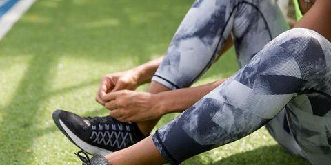 Footwear, Shoe, Grass, Human leg, Green, Leg, Joint, Ankle, Lawn, Sports gear,