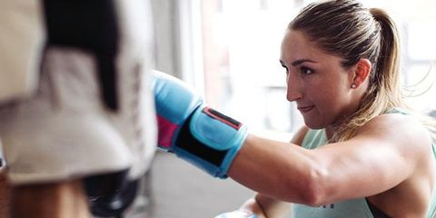 Boxing glove, Boxing, Arm, Muscle, Shoulder, Personal trainer, Sport venue, Physical fitness, Sports equipment, Room,